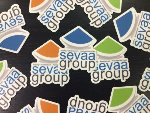 Sevaa Group stickers in orange, blue, and green on black table.