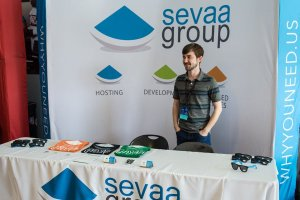 Cameron standing behind Sevaa Group table with swag.