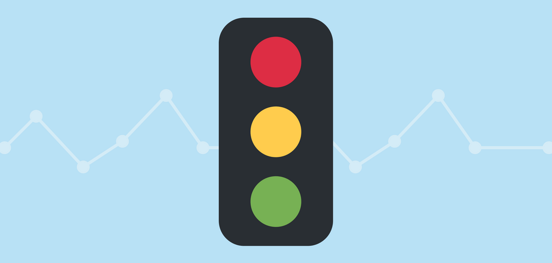 Traffic light in front of light blue line graph.